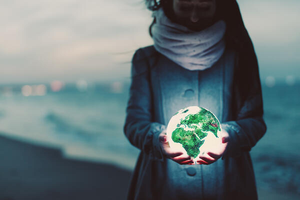 earth-globe-glowing-in-womans-hands-on-the-beach-a-TJ2ABV3_envato